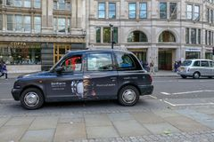 London, UK - August 3, 2017: London black cab parked at the sid. E of the road waiting for a passenger. Daytime shot of a street scene royalty free stock images