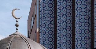 Close up of dome of the East London Mosque on Whitechapel Road, with the mosaic tiles of the London Muslim Centre to its side. royalty free stock photo