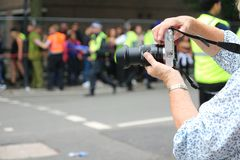 Elderly lady taking a picture of event stock image