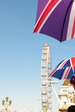 London, UK - 30 August 2016: London Eye in the background of de-focused umbrellas with England's flag. Royalty Free Stock Images
