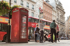 LONDON, UK - AUGUST 4, 2016:  Tourists by iconic red bus and red Stock Photography