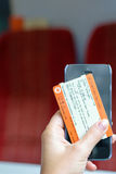 London, UK - 31 August 2016: Woman's hand holds a train ticket and a smartphone Stock Photo