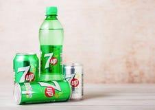 LONDON UK - AUGUSTI 03, 2018: Den plast- flaskan och aluminium cans av citrus sodavatten 7UP dricker på träbakgrund royaltyfria foton