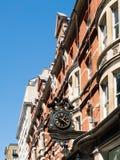 LONDON/UK - AUGUSTI 15: Gammal utsmyckad klocka på en byggnad i London Arkivbilder