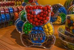 London UK - Augusti 7, 2018: Godisar för choklad för M&M ` s formade färgrika i nallebjörn behållare arkivfoton