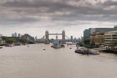 London UK - 31 Augusti 2016: Sikt av skeppet för HMS Belfast på flodThemsen med tornet av den London bron i bakgrunden Fotografering för Bildbyråer