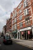 LONDON UK - AUGUSTI 14, 2010: typisk arkitektur, taxi och shoppar Royaltyfri Fotografi
