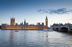 London, UK. Chrome blue sky reflections over the neo-gothic Houses of Parliament, iconic Big Ben (1834) and sweeping arches of Westminster bridge in the heart of Royalty Free Stock Image