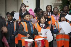 Children in orange waistcoats sing Christmas carols, collect money for charity Royalty Free Stock Images