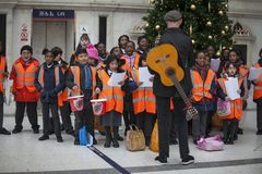 Children in orange waistcoats sing Christmas carols, collect money for charity Stock Photography