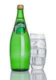 LONDON UK - DECEMBER 06, 2016: Flaska och exponeringsglas med is av Perrier kolsyrat vatten Perrier är ett franskt märke av butel Fotografering för Bildbyråer
