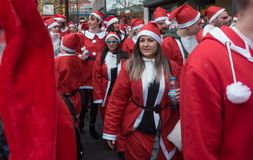 Santacon event in London. London, UK - December 2018 : Group of people dressed in santa outfits, holding and drinking alcoholic drinks while taking part in a stock image