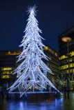 View of a modern LED Christmas tree standing next to the City H. LONDON, UK - DECEMBER 16, 2017: A large contemporary LED Christmas tree decorates the riverside royalty free stock photos