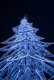 View of a modern glass Christmas tree standing next to the City. LONDON, UK - DECEMBER 16, 2017: A large contemporary LED Christmas tree decorates the riverside stock photo