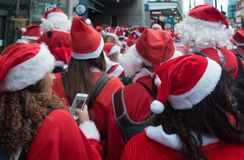 Santacon event in London. London, UK - December 2018 : Large crowd of people dressed in santa outfits, holding and drinking alcoholic drinks while taking part in royalty free stock images