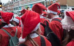 Santacon event in London. London, UK - December 2018 : Large crowd of people dressed in santa outfits, holding and drinking alcoholic drinks while taking part in royalty free stock image