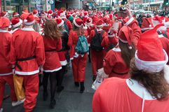 Santacon event in London. London, UK - December 2018 : Large crowd of people dressed in santa outfits, holding and drinking alcoholic drinks while taking part in stock photos