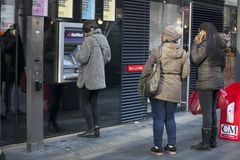 People stand in line to the ATM to withdraw money. London, UK - December 22, 2017: People stand in line to the ATM to withdraw money near Liverpool street Stock Photo