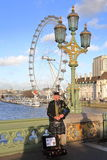 LONDON, UK - DECEMBER 31, 2015: Scottish musician playing bagpipes at sunset on Westminster Bridge with London Eye in the backgrou Stock Photos