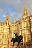LONDON UK - DECEMBER 31, 2015: Slotten av Westminster hus av parlamentet och statyn av konungen Richard I på solnedgången Royaltyfria Bilder