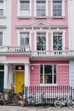 Bicycles by pastel pink coloured terraced house in Primrose Hill, London, UK royalty free stock photography