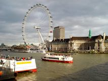 London, UK - February 1 2014: London Eye and Houses of Parliament, Thames river. stock photography