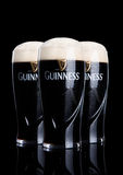 LONDON, UK - FEBRUARY 26, 2017: Glasses of Guinness original beer on black background. Guinness beer has been produced since 1759 Royalty Free Stock Images
