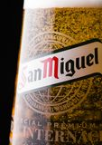 LONDON, UK - FEBRUARY 06, 2019: Original glass of San Miguel lager beer on dark wooden background. The San Miguel brand of beer is the leading brand of the San royalty free stock photography