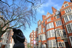 LONDON, UK - FEBRUARY 13, 2017: Red brick Victorian houses facades at Carlos Place in the borough of Westminster with a Statue Si Royalty Free Stock Image