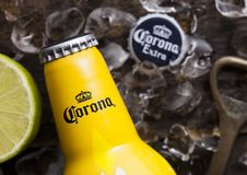 LONDON, UK - FEBRUARY 06, 2019: Steel Bottle of Corona Extra Beer Sunset Edition on wooden background with bottle opener and ice. Cubes. Corona, produced by royalty free stock photography