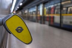In foreground, end of handrail at Southwark underground station, London showing TFL roundel. In background blurred train arrives a. London UK. In foreground, end stock images