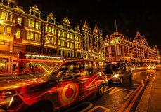 London UK - Harrods - in the night - long exposure. Harrods shopping mall and street - in London UK illuminated at night with car passing lights. Long exposure Stock Photography