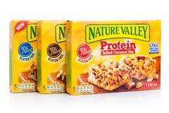 LONDON UK - JANUARI 02, 2018: Stänger för protein för granola för naturdal frasiga i askar med på vit Naturdalen är en allmän Mi Royaltyfria Foton