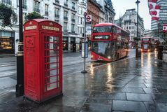 Telephone Booth and a modern double decker bus on the street in. London, UK- January 11, 2018:Telephone Booth and a modern double decker bus on the street in Royalty Free Stock Photos