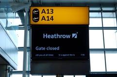 London UK, 03 Juli 2009: Baner av portar A13 och A14 i den Heathrow flygplatsen Stängd indiation för portar Arkivfoto