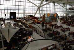 London UK, 03 Juli 2009: Många passagerare som väntar i vardagsrum av den Heathrow flygplatsen Olika ANNONSbaner omkring Arkivbild