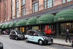 London black cabs. LONDON, UK - JULY 9, 2016: Black cabs wait at Harrods department store in London. The famous retail establishment is located on Brompton Road Stock Photo