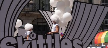 Float with people on board and decorated with balloons, on Regent Street during the Gay Pride Parade 2018 in London. London UK, July 2018 Float with people on Royalty Free Stock Images