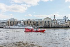 London / UK, July 15th 2019 - Thames Rockets sightseeing speed boat speeding down the Thames River in front of Butlers Wharf