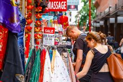 Tourists browsing outside a clothing and souvenir shop in Chinat stock image
