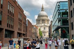 View of the Dome and facade of St. Pauls Cathedral through modern street. Historic and modern architecture next to each other. London, UK - July 21, 2018: View royalty free stock photo
