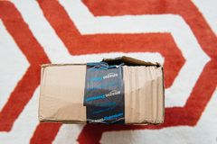 Above view of damaged Amazon Prime cardboard box. London, UK - Jun 3, 2016: Above view of damaged Amazon Prime cardboard box on living room carpet. Amazon Prime stock photo
