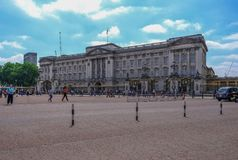 Front view of Buckingham Palace taken from the Memorial Gardens. London, UK - June 8, 2018: Front view of Buckingham Palace with tourists strolling around the Royalty Free Stock Image