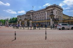 View of Buckingham Palace with tourists on a bright sunny blue s. London, UK - June 8, 2018: Front view of Buckingham Palace with tourists strolling around the Stock Photography