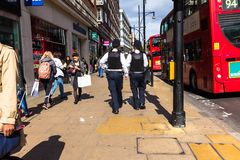 Oxford Street. Two unrecognizable police officers patrolling in the city. LONDON, UK - JUNE 9, 2015: Oxford Street. Two unrecognizable police officers in stock image