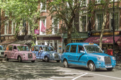 LONDON, UK - JUNE 11, 2014: A queue of multi coloured traditiona. L British taxis in a busy shopping street Royalty Free Stock Images