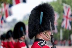 Amid tight security, Royal Guards in red and black uniform and bearskins line The Mall, London royalty free stock photos