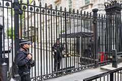 LONDON UK - JUNI 4th, 2017: Den beväpnade polisen bevakar portarna in i Downing Street i Westminster, London royaltyfri bild