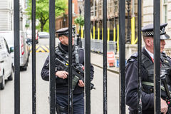 LONDON UK - JUNI 4th, 2017: Den beväpnade polisen bevakar portarna in i Downing Street i Westminster, London royaltyfria foton