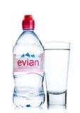 LONDON UK - MAJ 29, 2017: Flaska av Evian naturlig mineralvatten med exponeringsglas på en vit france gjorde Royaltyfri Bild